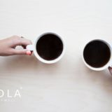 two people drinking coffee with qnola logo