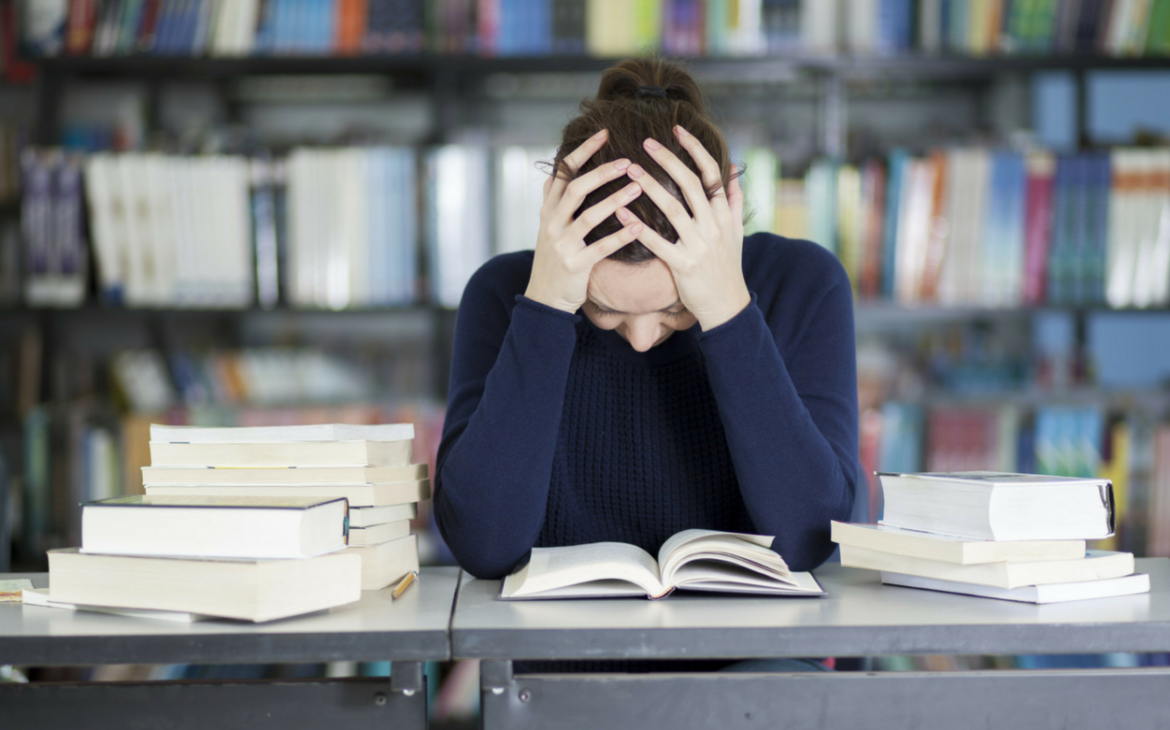 girl sat over books with head in hands experiencing period pain at school