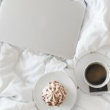 Comfy white bedding with cupcake , coffee and a laptop for a PMS binge-watch
