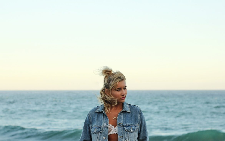 woman in bra and jacket stood beside the ocean