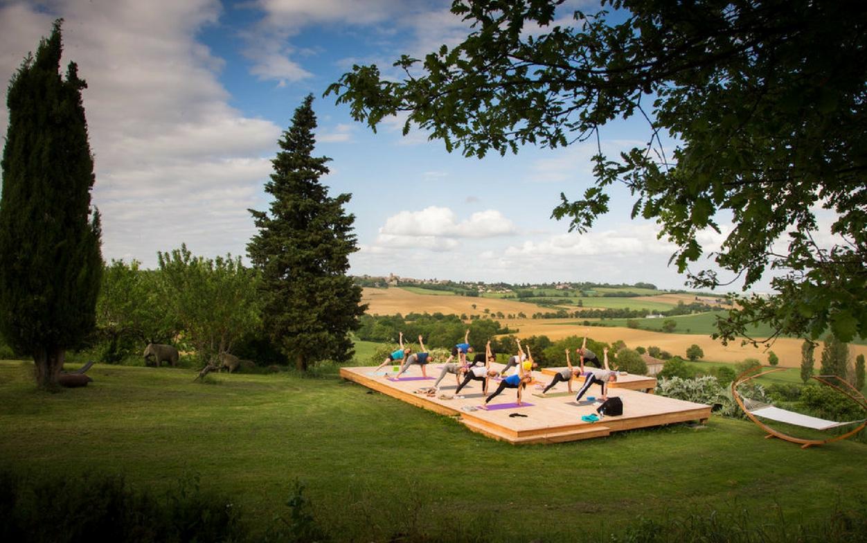 group of women doing yoga retreat outdoors