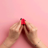 hands demonstrating how to fold a menstrual cup