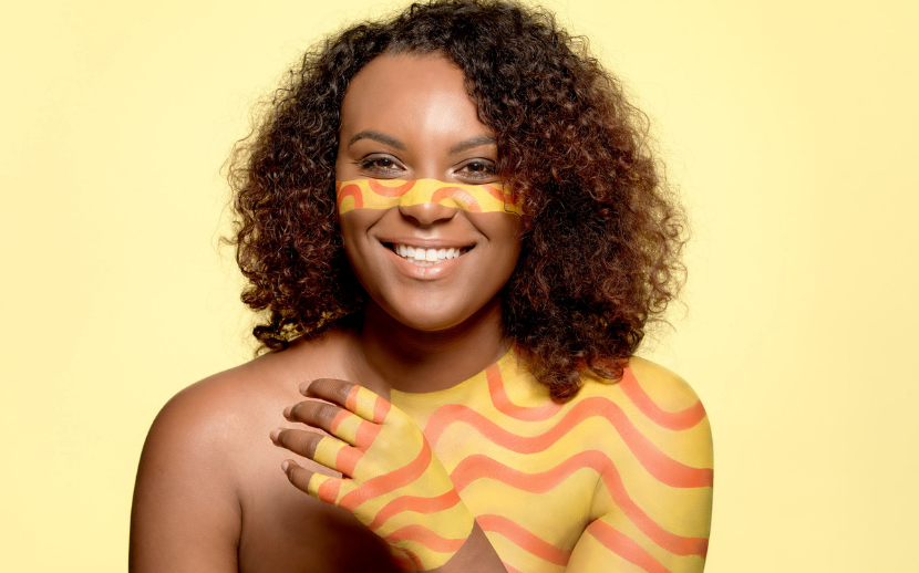 Period powerful activist model with yellow and orange body paint