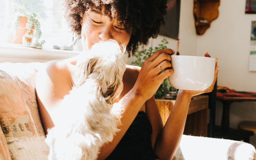 Happy smiling woman resting with cup of tea and pet dog