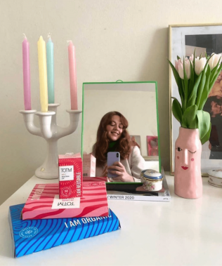 Dressing table set up and reflection of female in mirror with pink vase and pastel candles next to mirror