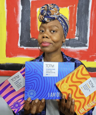 Female holding 3 TOTM product boxes against bright coloured artwork