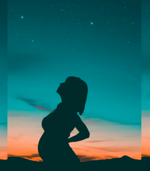 Shadow of a pregnant woman standing against the night sky