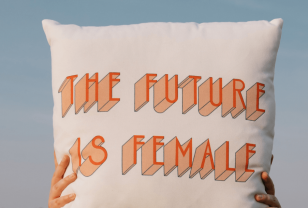 Hands holding up a cushion with the future is female in orange text on it against blue sky background