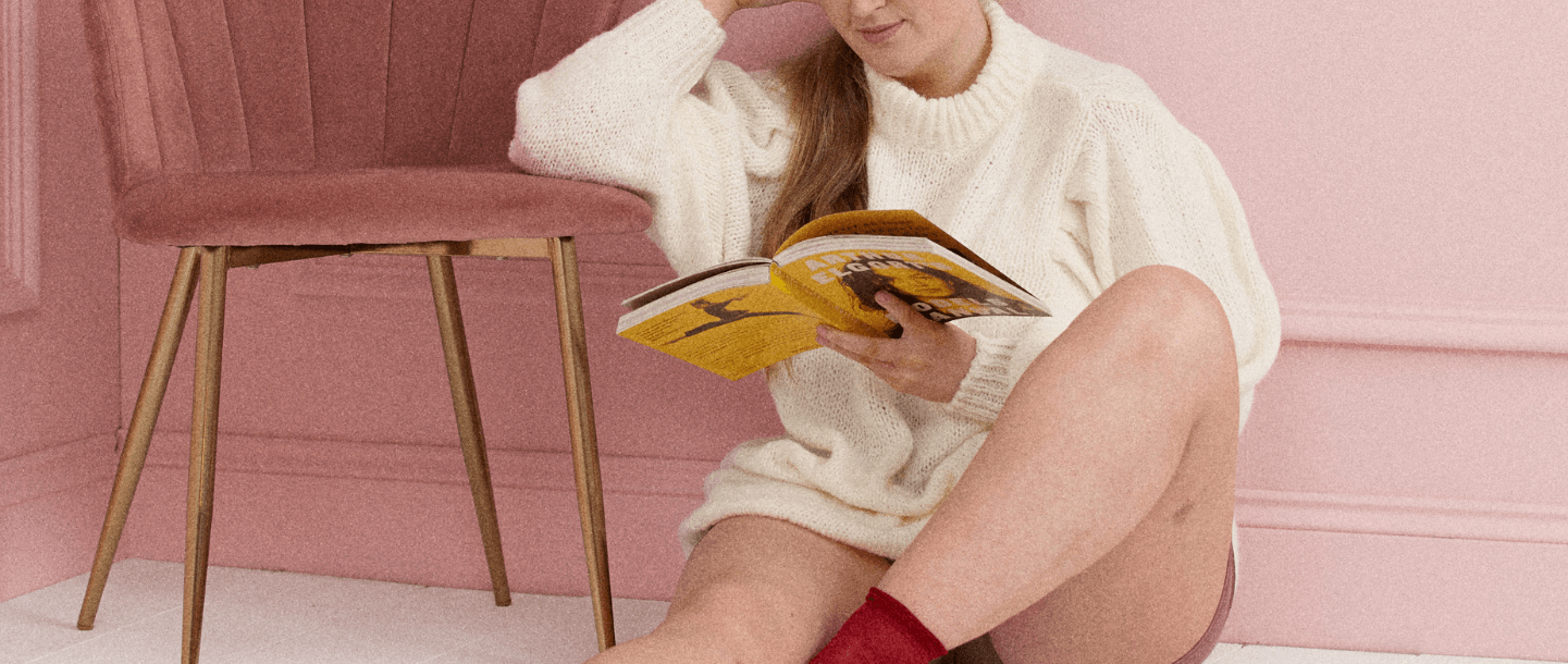 Blonde female in white knitwear dress sat on the floor reading a book with her elbow resting on a pink chair