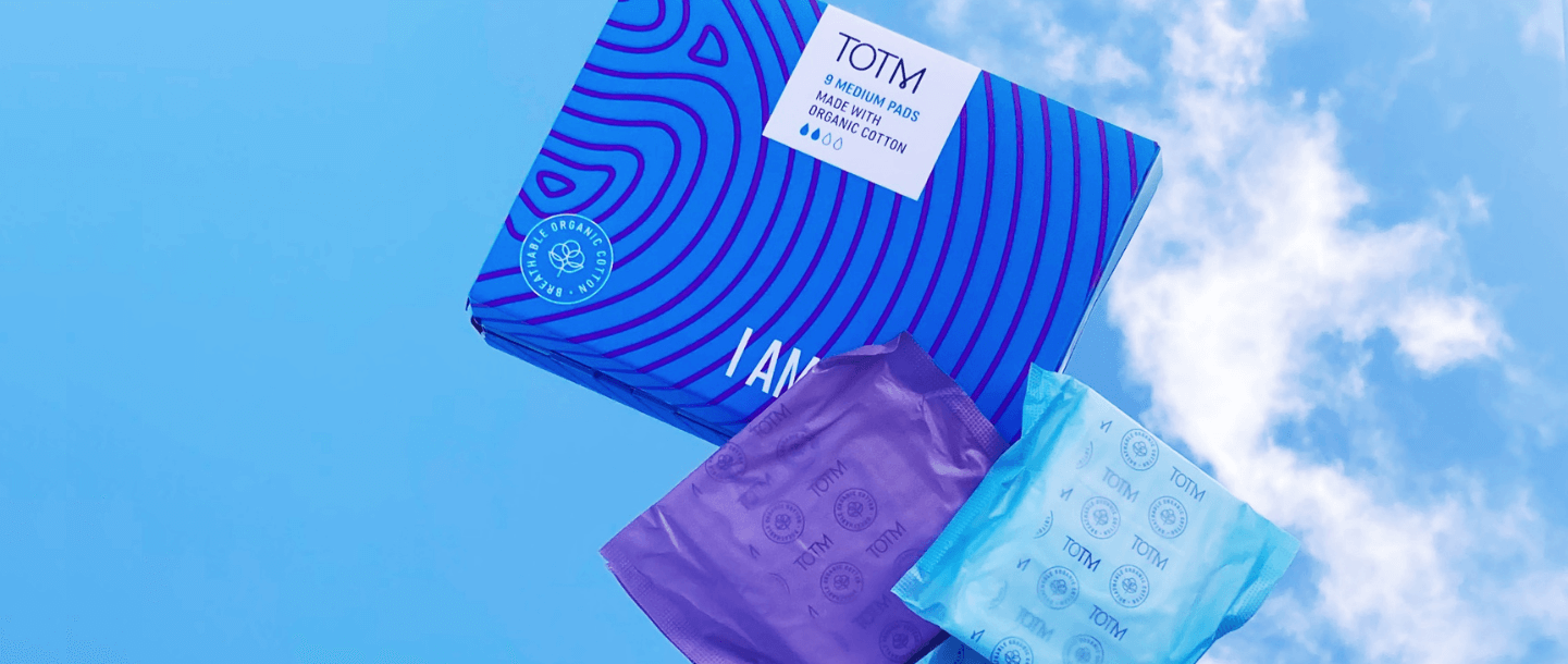 TOTM's medium flow organic cotton pads box next to medium and super pad in their wrapper on a blue background with sky reflection