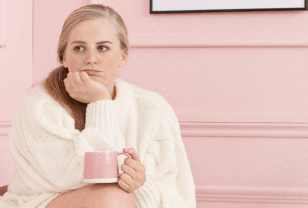 Blonde female is sitting in a pink room wearing a white knitted jumper and is resting her chin on her hand and drinking a herbal tea out of a pink mug which is resting on her knee to combat her period blues