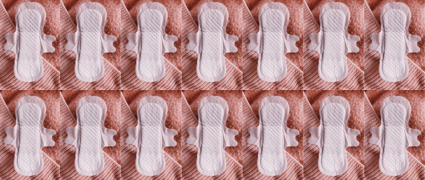 TOTM's organic cotton pad with wings out of the wrapper on a pink fabric background