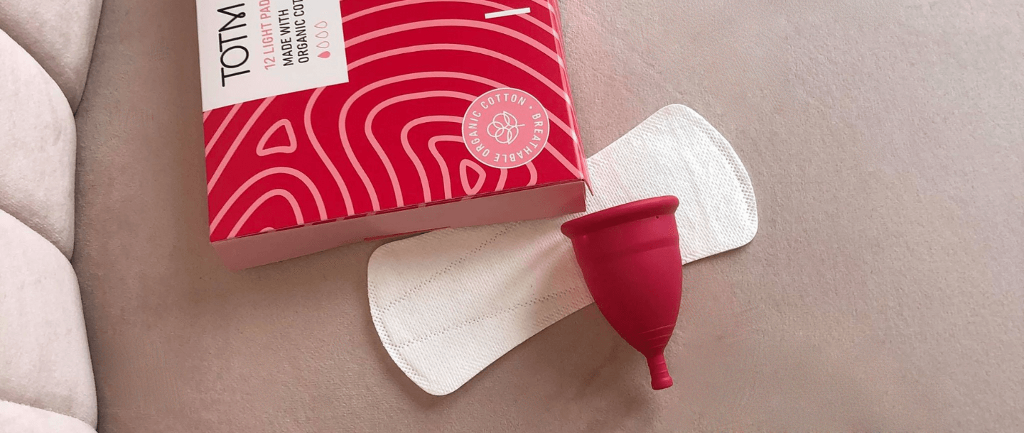 TOTM's reusable zero-waste menstrual cup, organic cotton liner and organic cotton light flow pads box on pink background