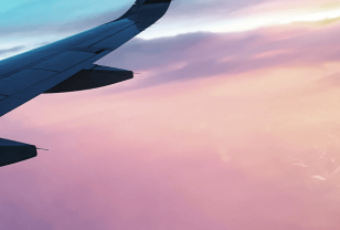Plane wing flying through pink sunset sky