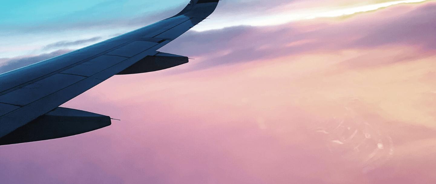 Plane wing flying through pink sunset sky