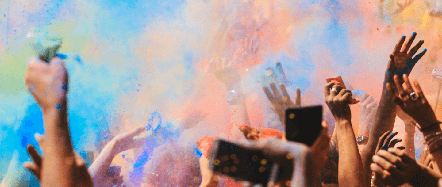 People dancing in colour powder during a festival