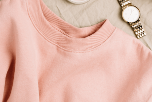 top half of a peach coloured sweatshirt on beige fabric background next to a watch and makeup