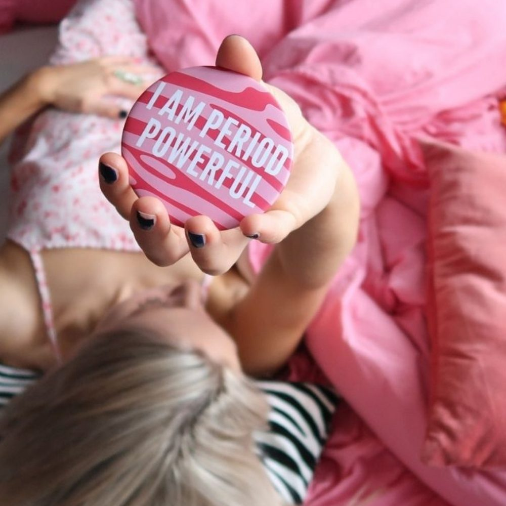 Blonde girl holding up period powerful cosmetic mirror lying down on pink duvet