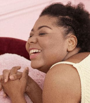 A black female laying on her stomach on a pink bed in a pink room holding her hands. She is smiling and wearing a yellow top with pink shorts
